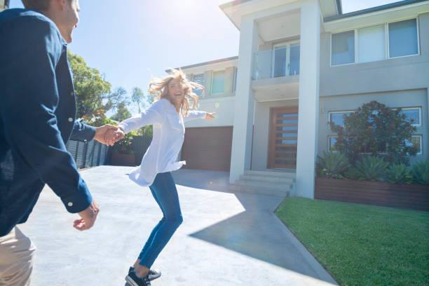 Paar läuft freudig in ihr neues Zuhause – Foto