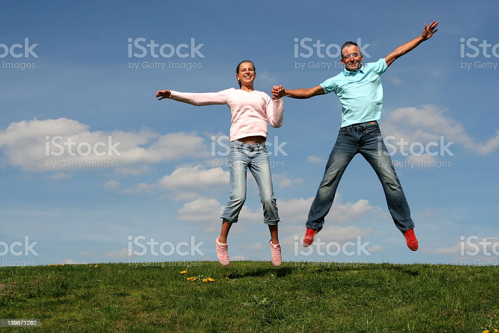 Couple jumping against blue sky royalty-free stock photo