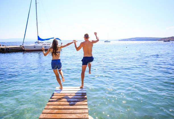 couple jumping into water - jump pool, swimmer imagens e fotografias de stock