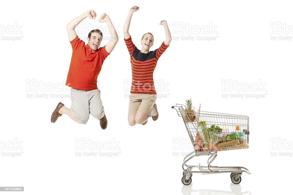 Couple jumping near a shopping cart royalty-free stock photo