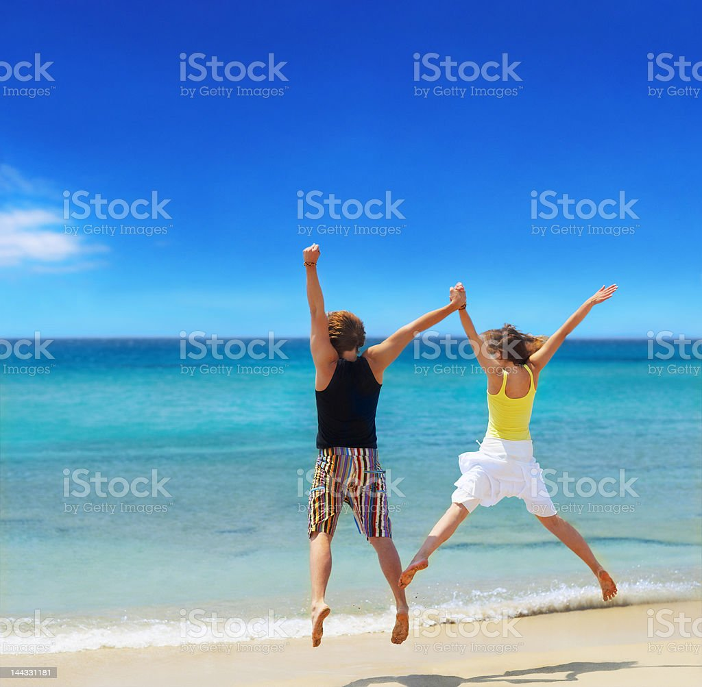 Couple jumping on the beach royalty-free stock photo