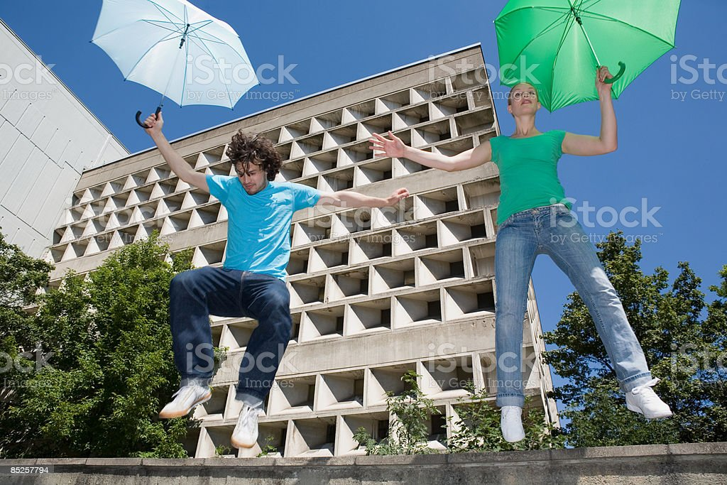 Couple jumping with umbrellas royalty-free stock photo