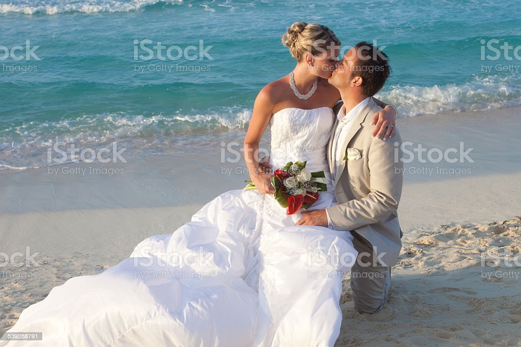 Couple Just Married Kissing On A Tropical Beach stock photo