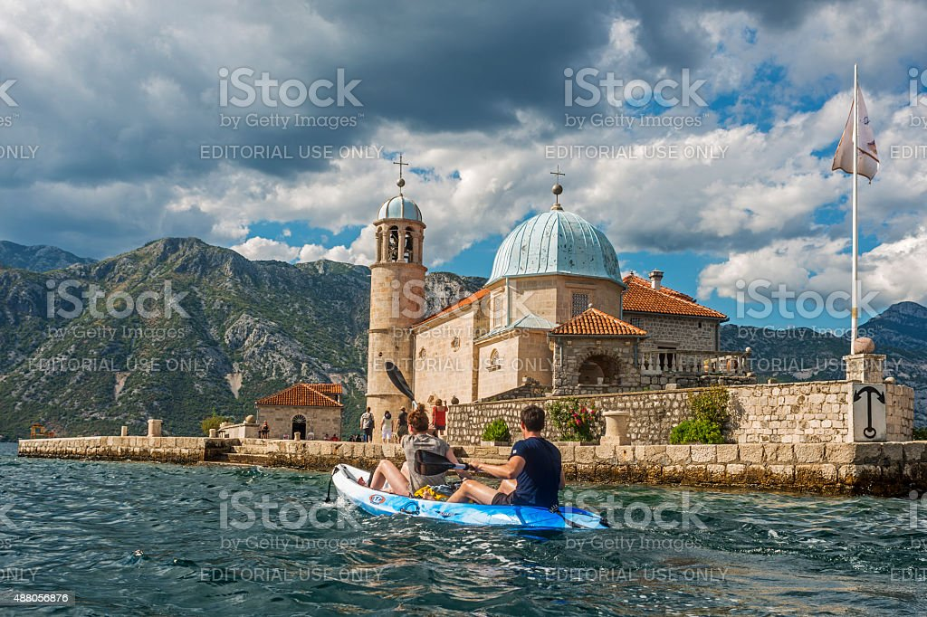 Couple kayaking in front of Our Lady of the Rocks stock photo