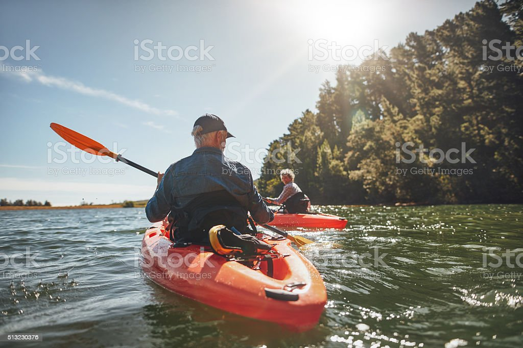 Couple kayaking in the lake on a sunny day stock photo