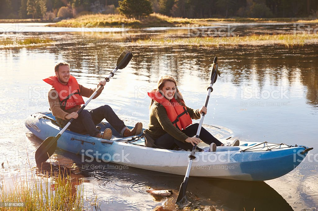 Couple kayaking on lake, front view, Big Bear, California stock photo