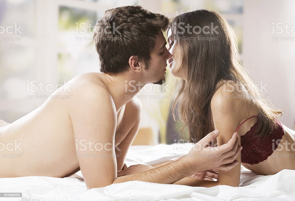 Couple kissing and hugging on bed in bedroom stock photo