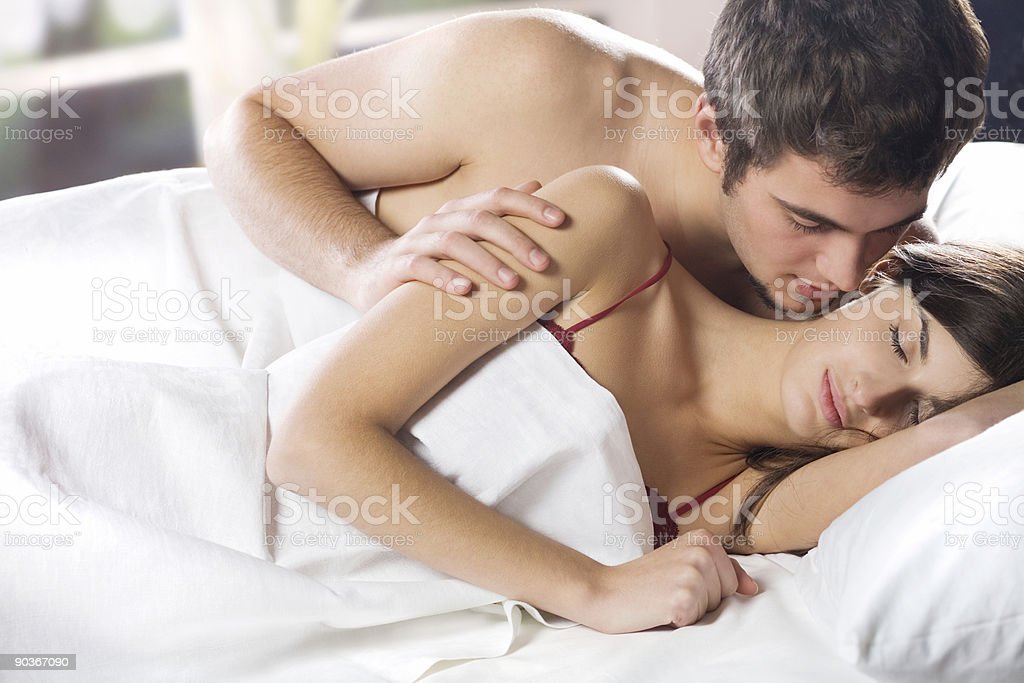Couple kissing and hugging on the bed in bedroom stock photo