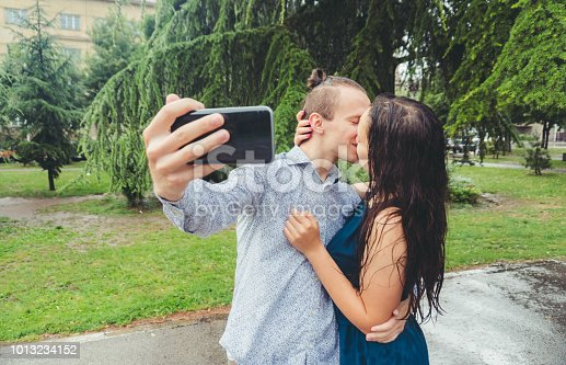 Man and woman in love taking selfies in the rain