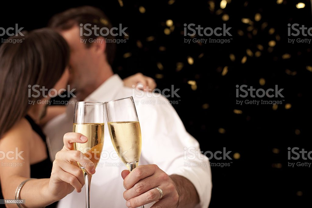 Couple Kissing and Toasting Champagne Flutes for New Year's Eve royalty-free stock photo