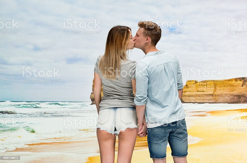 Couple kissing at the beach stock photo
