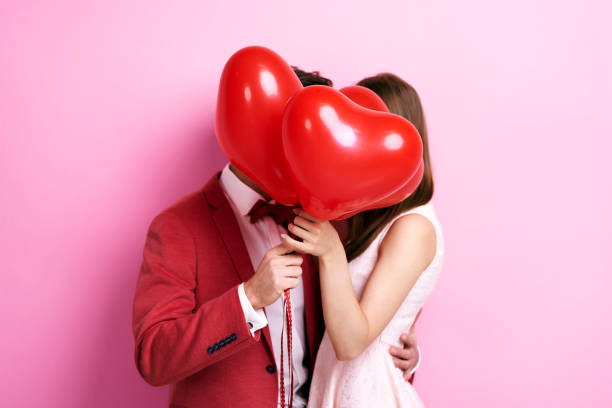couple kissing behind balloons - falling in love stock pictures, royalty-free photos & images
