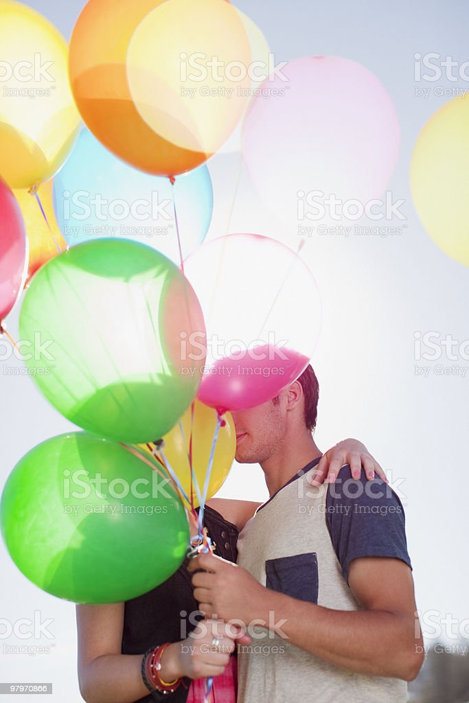 Couple kissing behind balloons royalty-free stock photo