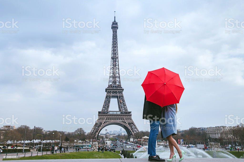 couple kissing behind umbrella in Paris stock photo