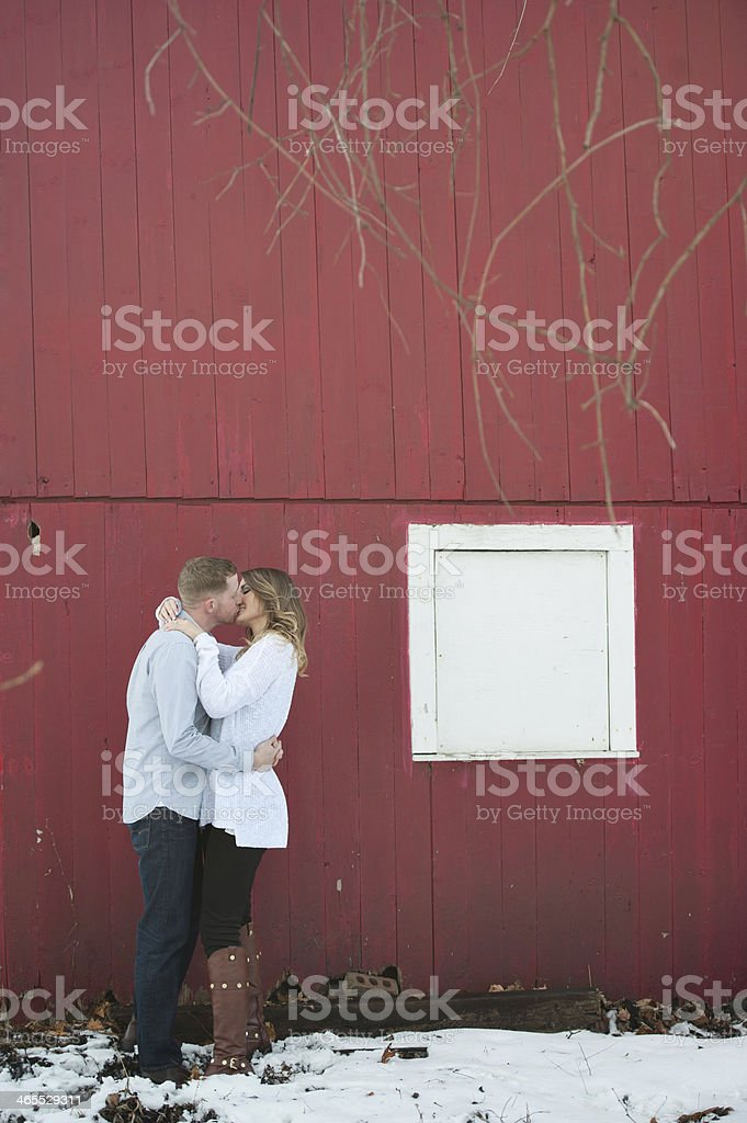 Couple Kissing by Barn stock photo