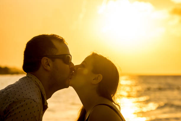 Couple kissing by the beach. stock photo