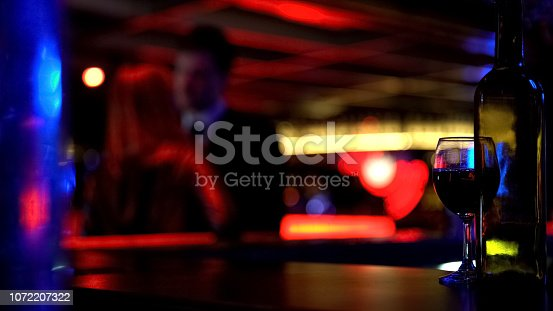 istock Couple kissing heartily at meeting, dating in nightclub, blurred background 1072207322