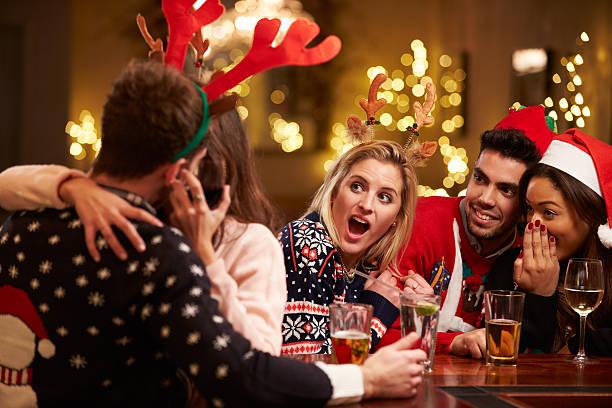カップルのキスで、ご友人とバーのクリスマスのお飲物をお楽しみください。 - 社内パーティ ストックフォトと画像