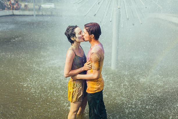Couple kissing in fountain Couple kissing in the fountain  wet clothing women t shirt stock pictures, royalty-free photos & images