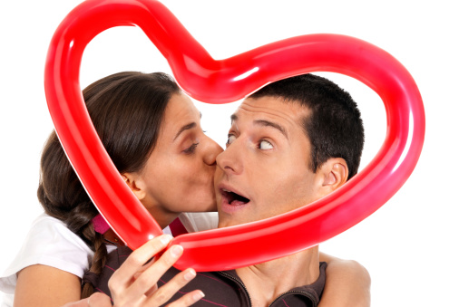 518335358 istock photo Couple kissing in front of balloon heart 154221207