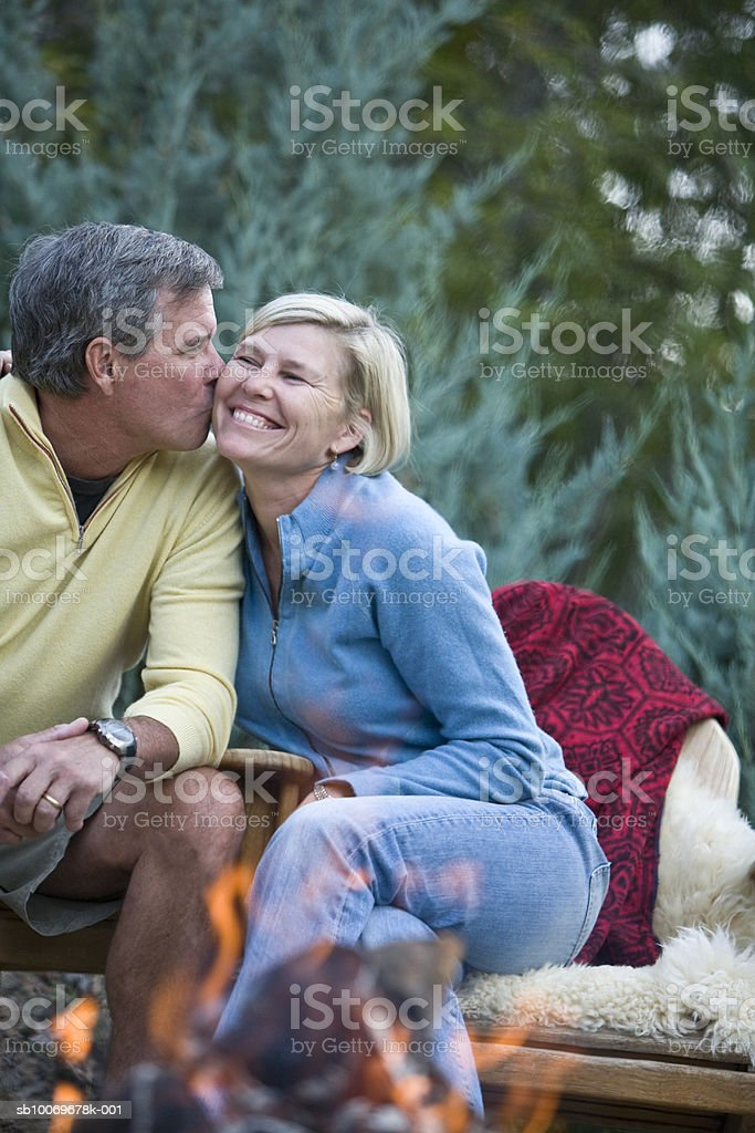 Couple kissing in front of campfire, smiling foto de stock libre de derechos