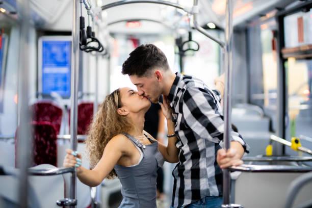 Couple kissing in public transportation bus