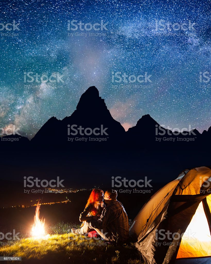 Couple kissing near a c&fire and tent under the stars royalty-free stock photo & Couple Kissing Near A Campfire And Tent Under The Stars Stock ...