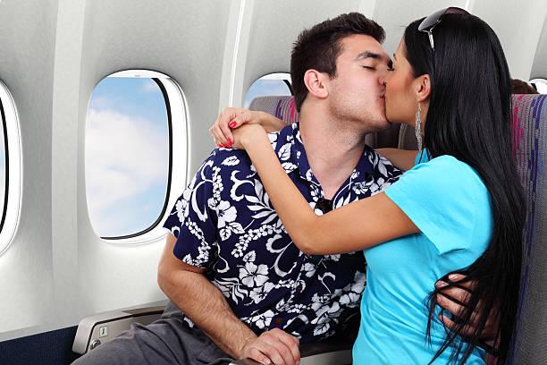 Couple Kissing On Airplane stock photo