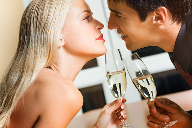 Couple kissing on romantic date or celebrating together at restaurant stock photo