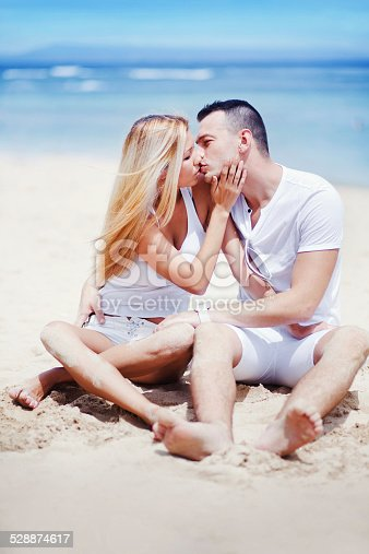 1065243116 istock photo Couple kissing on the beach 528874617
