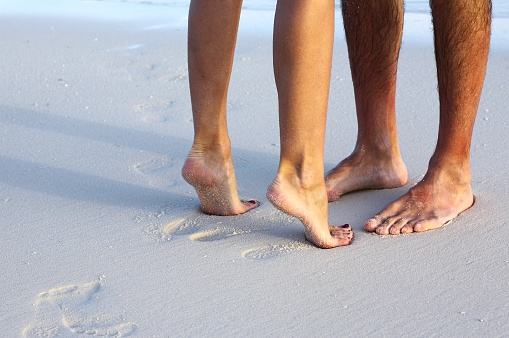 Couple Kissing On The Beach With View Of The Feet Stock Photo - Download Image Now