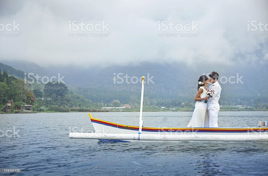 A couple kissing on their wedding day, standing on a boat royalty-free stock photo
