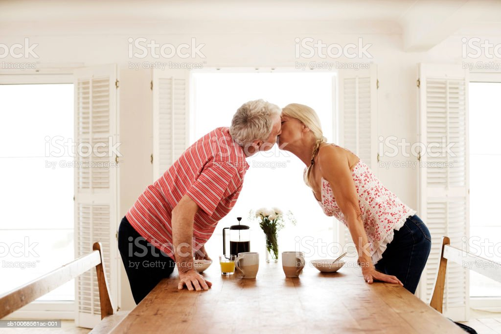 Couple kissing over dining room table foto de stock royalty-free