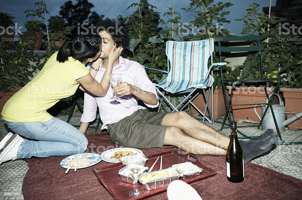 Couple kissing over romantic meal on terrace royalty-free stock photo