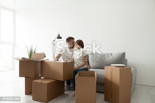 938682826istockphoto Couple kissing sitting on sofa in living room with boxes 916092468