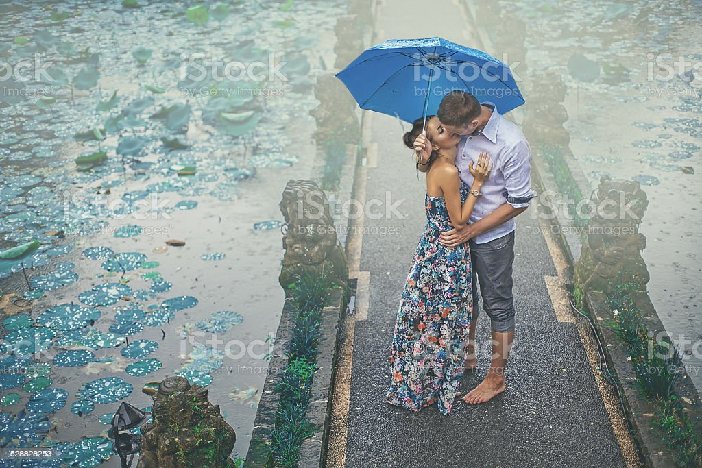 couple kissing under the rain on their first date Bali Adult Stock Photo