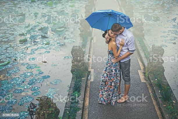 Couple Kissing Under The Rain On Their First Date Stock Photo - Download Image Now