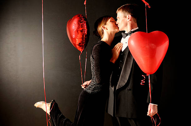 Couple kissing with heart shaped balloons stock photo