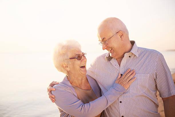 couple laughing after funny joke - mão no peito imagens e fotografias de stock