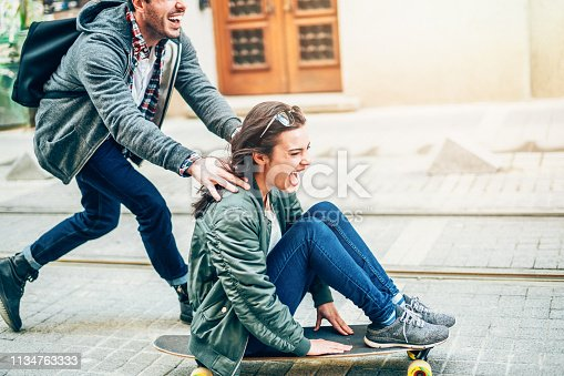 Young couple on street have fun on skateboard