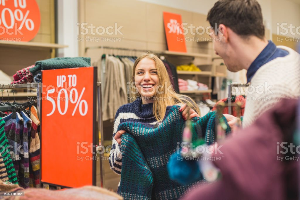 Couple laughing and shopping in store stock photo