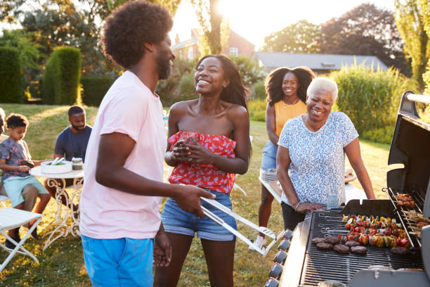 Couple laughing at a multi generation family barbecue Couple laughing at a multi generation family barbecue family bbq stock pictures, royalty-free photos & images