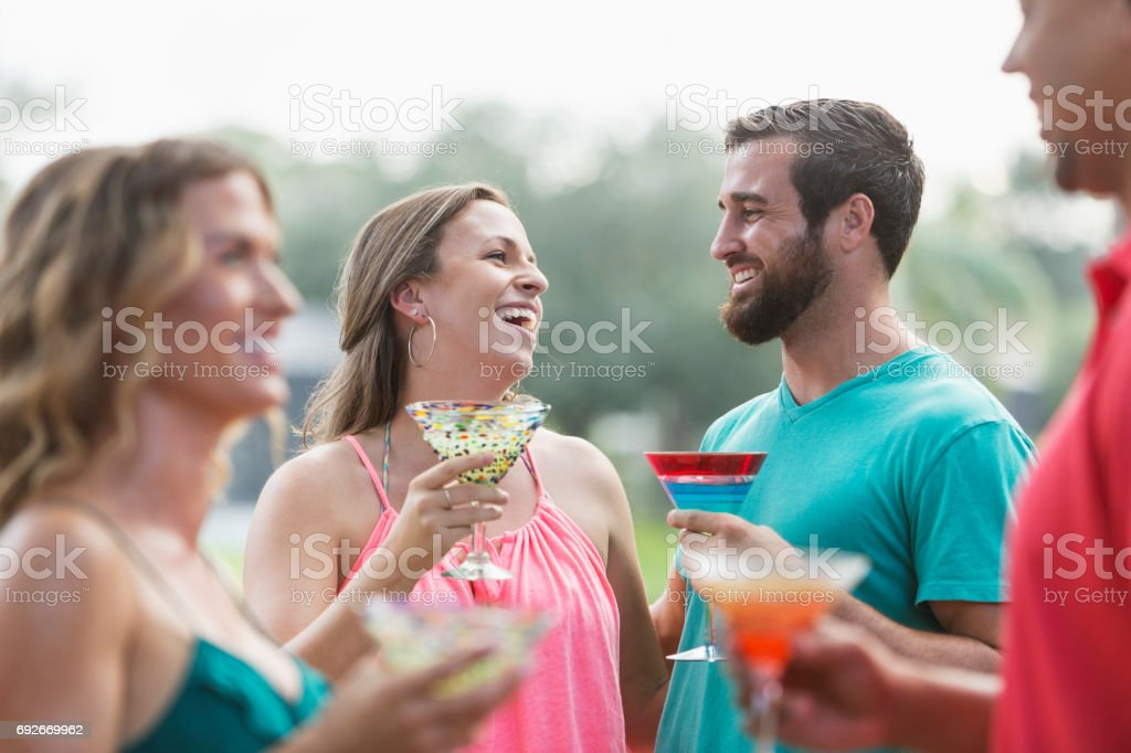 Couple laughing at a party, with cocktails stock photo