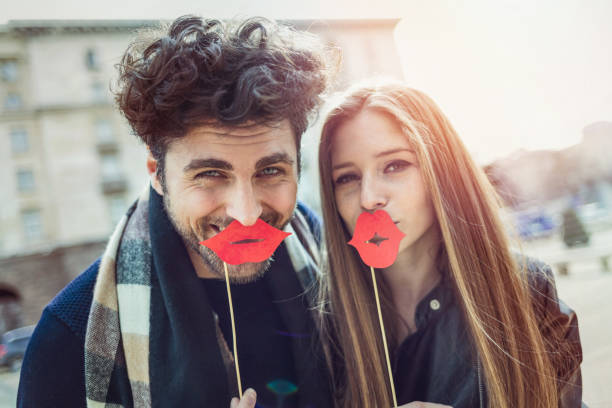 Couple laughing at camera and holding large red lips stock photo