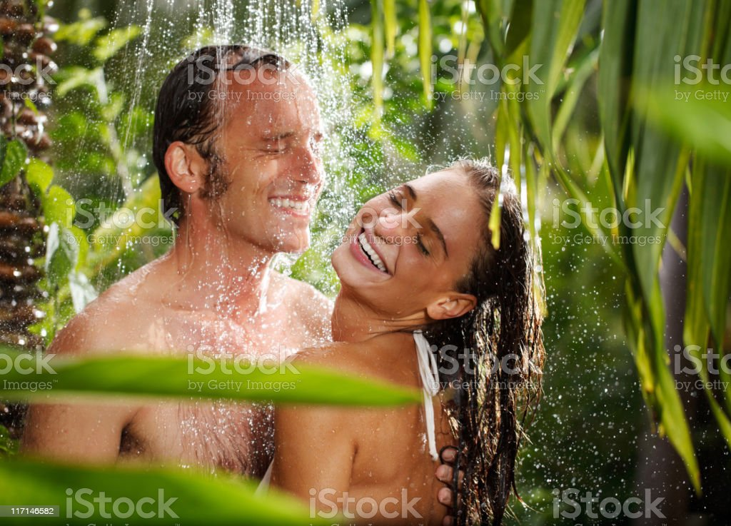 Couple laughing in outdoor shower. royalty-free stock photo