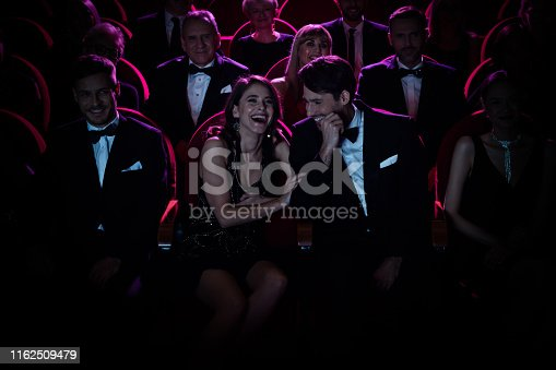 Couple laughing while enjoying opera. Happy man and woman are watching theatrical performance during weekend. They are sitting amidst crowd.
