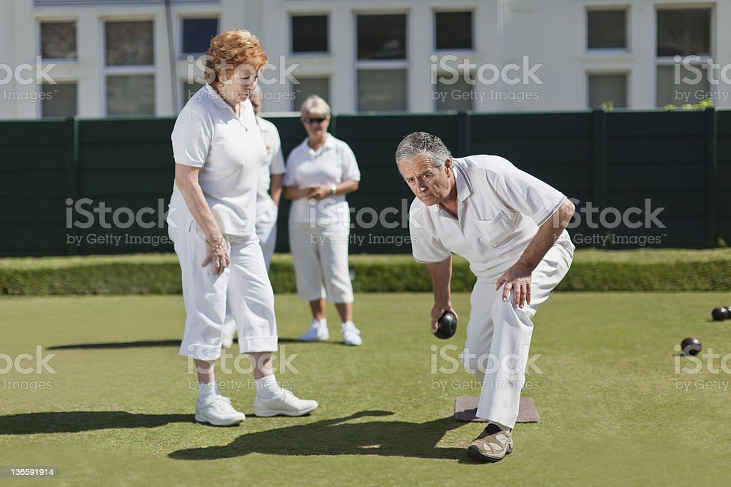 Couple lawn bowling on grass stock photo