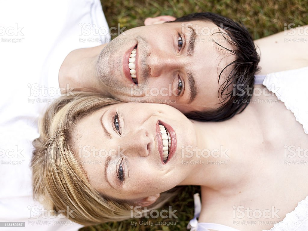 Couple laying in the grass stock photo