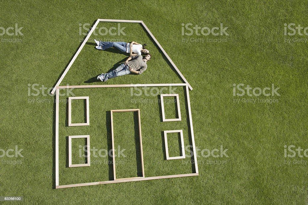 Couple laying inside house outline royaltyfri bildbanksbilder
