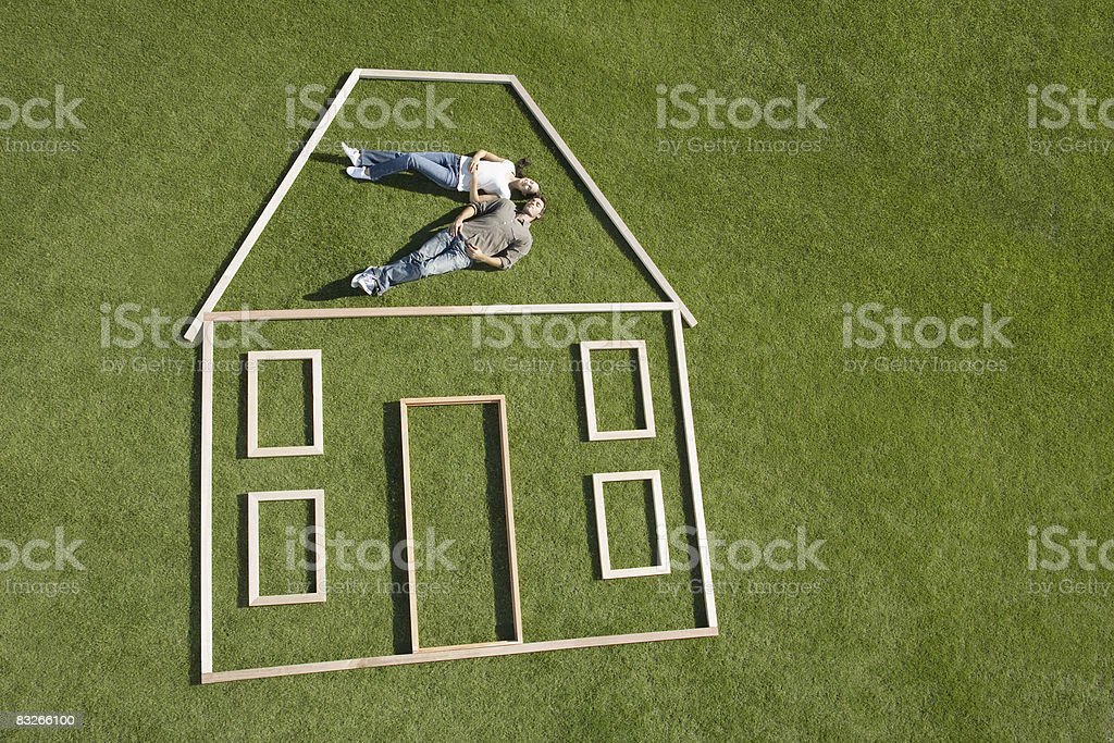Couple laying inside house outline stock photo